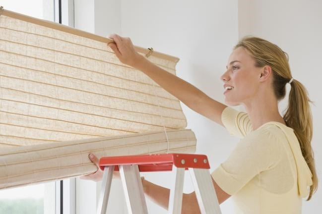 woman fixing window blinds